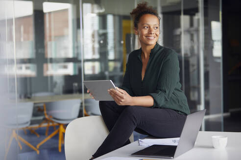 Portrait of smiling businesswoman with digital tablet sitting on desk looking at distance - RBF07782