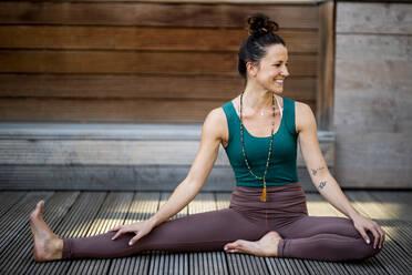 Smiling woman looking away while exercising on hardwood floor against house - DAWF01624