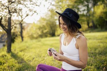 Smiling woman wearing hat burning incense while sitting on grassy land in park - DAWF01642