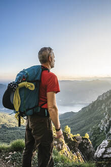 Hiker with backpack looking at mountains against clear sky during sunset, Orobie, Lecco, Italy - MCVF00456