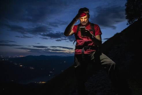 Male hiker checking map over smart phone while standing on mountain at night, Orobie, Lecco, Italy - MCVF00459