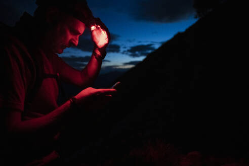 Man with headlamp checking map over smart phone at night, Orobie, Lecco, Italy - MCVF00462