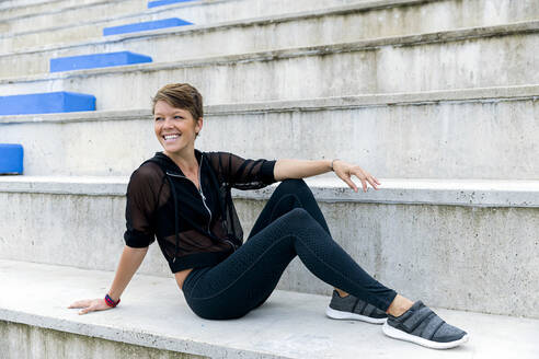 Athletic woman sitting on stairs - LVVF00068