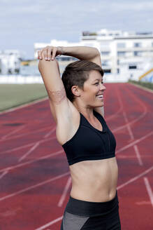 Athletic woman stretching her arm on tartan track - LVVF00110