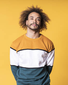 Handsome young man with curly hair standing against yellow background - SNF00344
