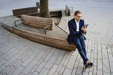 Smiling businessman sitting on wooden bench using tablet - JOSEF00832