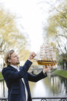 Businessman holding model ship at a channel - JOSEF00838