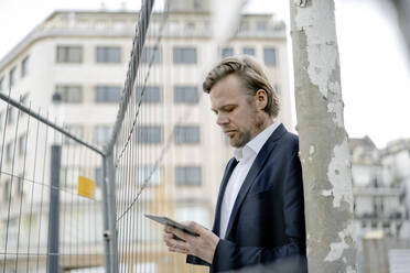 Businessman using tablet at a hoarding in the city - JOSEF00862