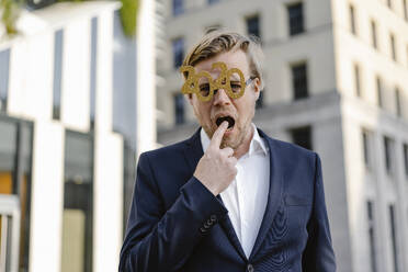 Businessman wearing 2020 comedy glasses in the city putting finger in the mouth - JOSEF00886