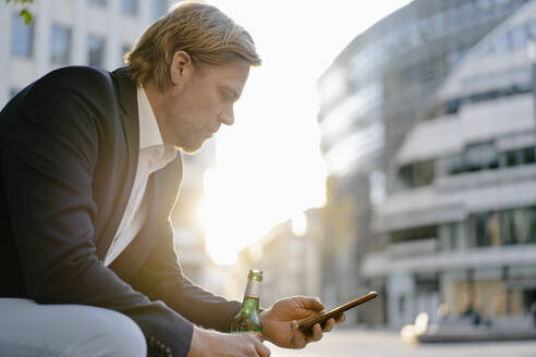 Businessman sitting on a bench in the city at sunset with a bottle of beer and smartphone - JOSEF00919