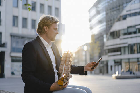 Businessman sitting on a bench in the city at sunset with model ship and smartphone - JOSEF00922