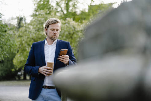 Businessman with takeaway coffee using smartphone in city park - JOSEF00937