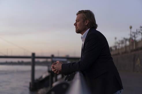Businessman standing at the riverside at dusk looking away - JOSEF00940