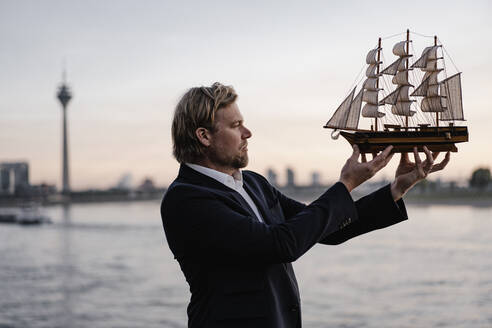 Businessman holding model ship at the riverside at dusk - JOSEF00943