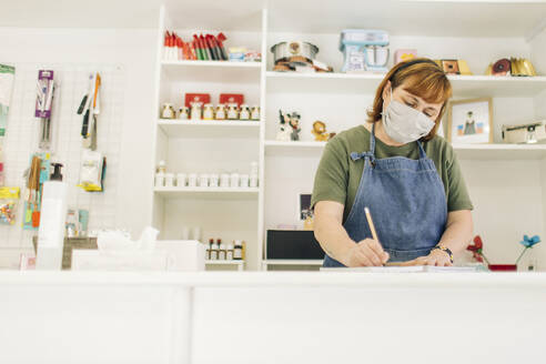Female baker wearing mask writing in book on checkout counter at shop - GMLF00234