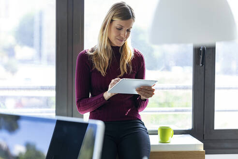 Businesswoman using digital tablet while sitting against window in office - JSRF00960