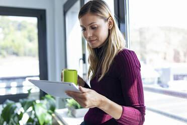 Businesswoman holding coffee mug using digital tablet in office - JSRF00966