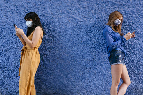Female friends wearing masks using smart phones while standing by blue wall in city - TCEF00766