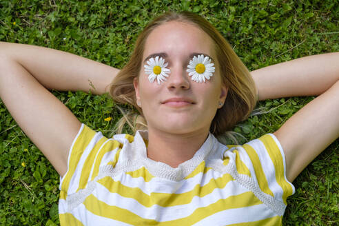Close-up of young woman with oxeye daisies on eyes lying over grassy land in park - LBF03081
