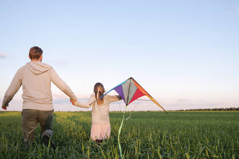 Girl holding kite walking with father amidst plants on green landscape - EYAF01160