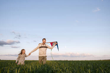 Cheerful father and daughter with kite running on green landscape against sky - EYAF01163