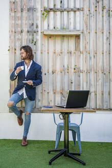 Fashionable young businessman drinking espresso by laptop on table against wooden wall at cafe - DLTSF00784