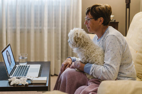 Ill senior woman discussing with doctor over video call while holding dog at home - XLGF00233
