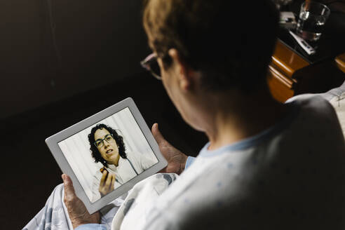Elderly woman discussing over video call through digital tablet with doctor in bedroom - XLGF00245