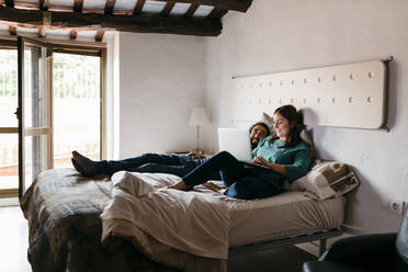 Couple watching movie sitting on bed at home - JRFF04535