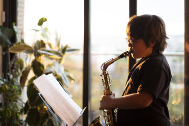 Boy exercising to play the saxophone at home in the evening - VABF03086