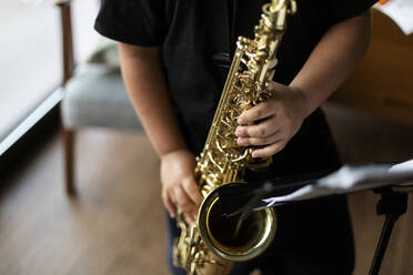 Crop view of boy exercising to play the saxophone at home - VABF03092