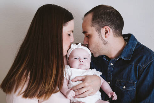 Parents kissing baby girl against wall at home - EBBF00215