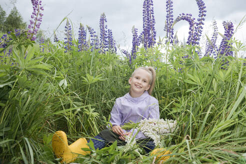 Portrait of happy girl sitting in front of lupine field with bunch of picked flowers - EYAF01175