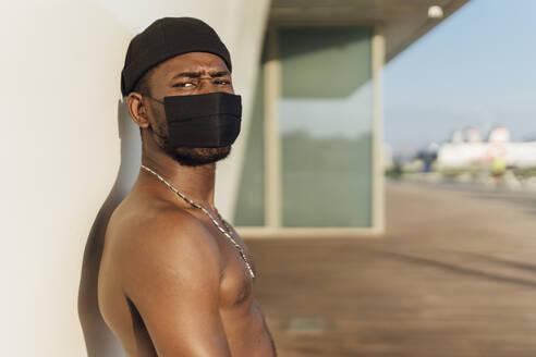 Young shirtless man wearing face mask against wall during coronavirus - EGAF00238