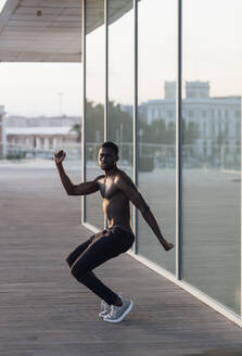 Young shirtless man dancing by window glass - EGAF00253