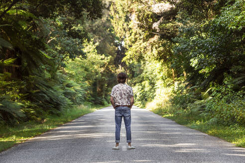 Man standing on road amidst trees in forest - WVF01818