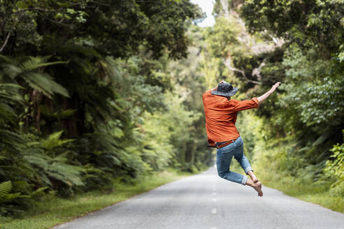 Excited man jumping on country road amidst trees in forest - WVF01833
