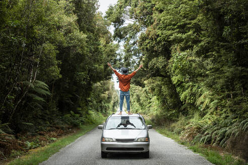 Young man with arms outstretched standing on car roof at country road - WVF01848