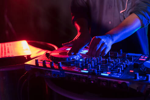 Close-Up Of Man Playing Music On Audio Equipment In Nightclub - EYF07504