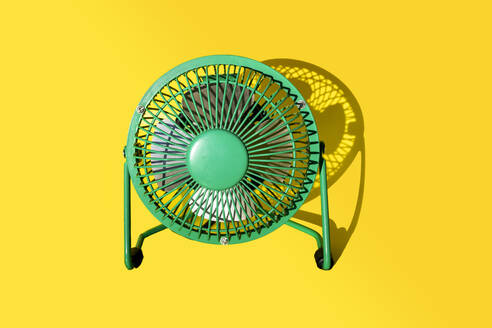 Green electric fan against yellow background - GEMF03881