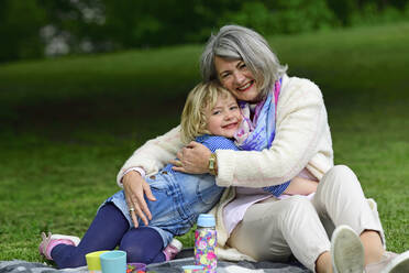 Affectionate grandmother and granddaughter embracing while sitting in public park - ECPF00963