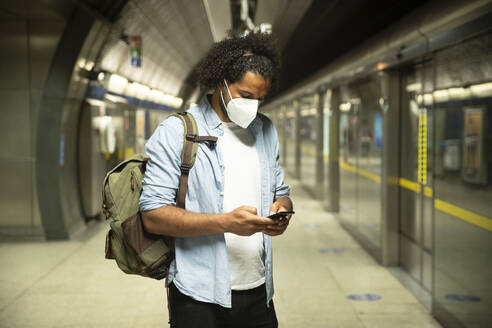 Young man wearing protective mask standing at underground station platform, London, UK - PMF01115