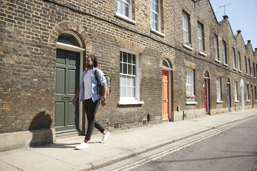 Young man walking on pavement in front of residential houses, London, UK - PMF01118