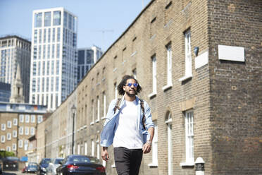 Portrait of young man with backpack walking on residential street, London, UK - PMF01121