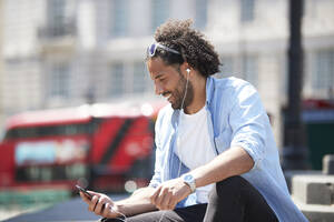 Portrait of smiling young man sitting outdoors listening music with cell phone and earphones, London, UK - PMF01130