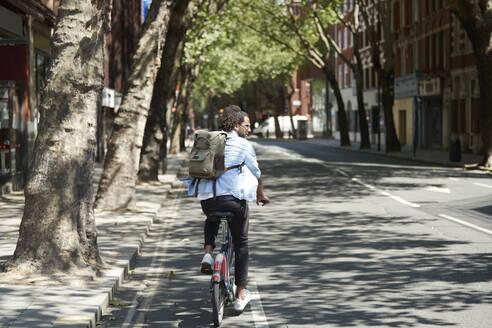 Back view of young man riding rental bike on bicycle lane, London, UK - PMF01136