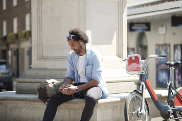 Young man with rental bike listening music with cell phone and earphones in the city, London, UK - PMF01139