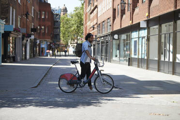 Young man crossing the street with  rental bike, London, UK - PMF01142