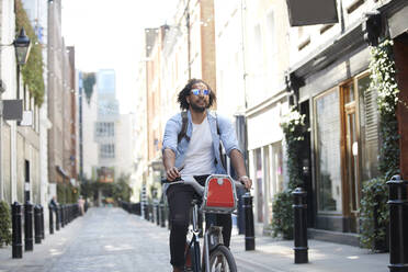 Portrait of young man riding on rental bike in the city, London, UK - PMF01145