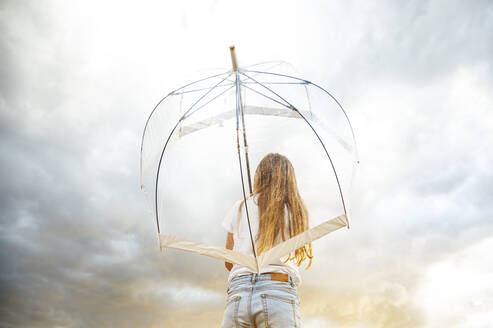 Blond girl holding transparent umbrella during monsoon - JCMF00917